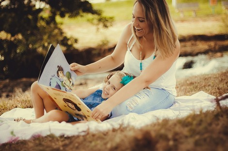 Happy mom with her daughter reading a picture book outdoor