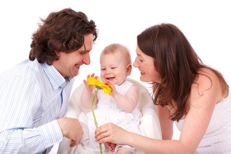 Happy parents with a new baby, examining a yellow flower